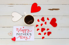 Mother`s Day vintage overhead composition of note with love confession. Hearts and coffee mug on wooden background Royalty Free Stock Photography