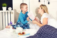 The son brought his mother breakfast in bed and presents a painted postcard. Mother`s day.Women`s day. royalty free stock photos