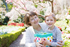 Mother's day. Young beautiful mother and her little son giving her a gift for mother's day enjoying time together at spring time in the park Royalty Free Stock Image