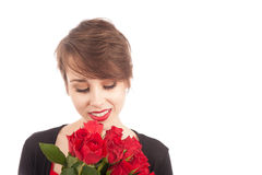 Mother's Day. A young woman in a red dress is enjoying a bunch pf roses Royalty Free Stock Photo