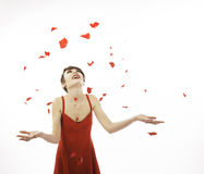 Mother's Day. A young woman in a red dress is enjoying the falling rose petals Stock Photo