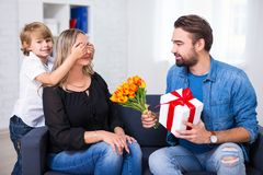 Mother`s or female day concept - little son and father giving fl. Owers and gift to wife and mother at home royalty free stock images