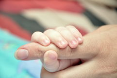 Mother's finger in the hand of  child Stock Photos