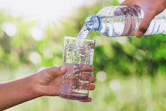 mother& x27; s geeft het hand gietende drinkwater in de fles van de glasvorm royalty-vrije stock fotografie