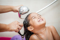Mother's hand pours water from shower to wash hair. Mother's hand pours water from shower to wash little girl's hair Stock Photography