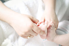 Mother's hands and child's feet Stock Images