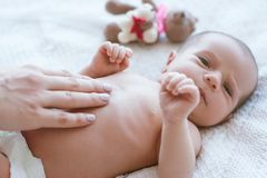Mother`s hands gently stroke the newborn baby Royalty Free Stock Photos