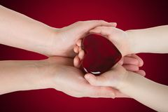 Mother's hands holding baby hands with heart Royalty Free Stock Photo