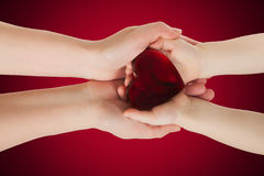 Mother's hands holding baby hands with heart Royalty Free Stock Image