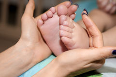 Mother`s hands holding tiny baby feet. Gentle mother`s hands holding tiny baby feet Stock Photo