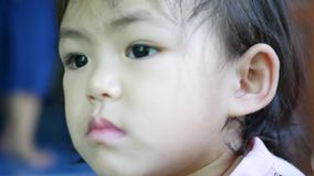 A mother`s hands using a cotton swab to clean her little Asian baby girl`s ear canals. Cleaning inside children`s ears could cause a wax buildup in the first stock video