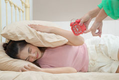 Mother`s holding an alarm clock and waking up her teenage daught Royalty Free Stock Photography