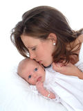 A Mother's Kiss. Newborn looking toward camera as mother kisses her Royalty Free Stock Photography