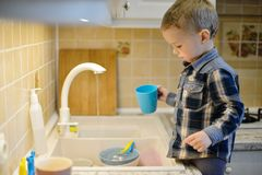 Mother`s little helper. Little boy helping mother washing dishes in the kitchen Royalty Free Stock Photography