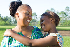 Mother's love. Young happy african mother and her teen daughter Stock Image