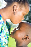 Mother's love. Happy african mother kissing son showing her love to the kid Stock Photography