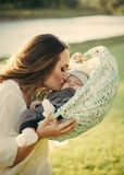 Mother`s love. Mother woman kiss baby son in basket on natural landscape Royalty Free Stock Photo