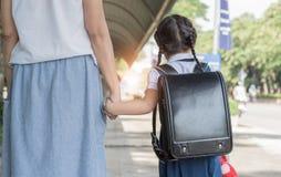 Mother& x27; s ręki prowadzenie jego dziecko córka iść szkoła fotografia stock