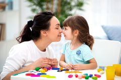 Mother`s tenderness and love. Mom gently kisses her daughter in the nose. Woman and little girl mold from plasticine.  royalty free stock image