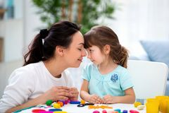 Mother`s tenderness and love. Mom gently kisses her daughter in the nose. Woman and little girl mold from plasticine.  royalty free stock photography