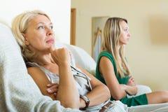 Mother and sad adult daughter having quarrel. Mature mother and sad adult daughter having quarrel stock photos