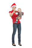 Mother in Santas hat holding baby and alarm clock Stock Photography