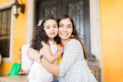 Mother Saying Bye With A Hug To Schoolgirl. Portrait of attractive nanny smiling while hugging cute girl before leaving for kindergarten royalty free stock photography