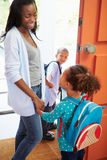 Mother Saying Goodbye To Children As They Leave For School. Holding Hands Smiling At Each Other Stock Photography