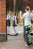 Mother saying goodbye to her daughters going to school. Portrait of mother saying goodbye to her daughters going to school stock photography
