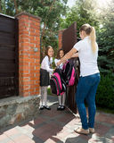 Mother saying goodbye to her daughters going to school. Young mother saying goodbye to her daughters going to school royalty free stock photos