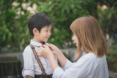 Mother saying goodbye to her son. Asian mother saying goodbye to her son as he leave for School,back to school concept royalty free stock photo
