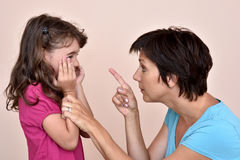 Mother scolding a daughter. Angry mother scolding a scared daughter Stock Photography