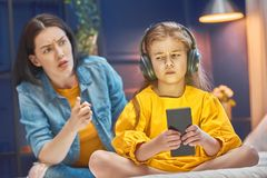 Mother is scolding her child. Girl playing on phone. Family relationships Royalty Free Stock Image