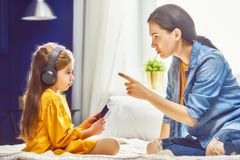 Mother is scolding her child. Girl playing on phone. Family relationships Royalty Free Stock Photography
