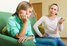 Mother scolding teenage son. Angry mother scolding naughty teenage son in home interior. Focus on boy Stock Images