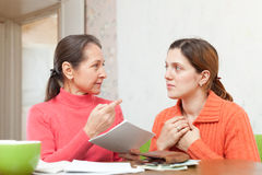 Mother scolds daughter for payments bills or credits. Mature mother scolds adult daughter for payments bills or credits stock photography