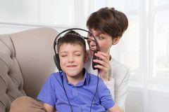 Mother screaming to her son while he listening music and doesn`t listen. Mother screaming to her teen son while he listening music and doesn`t listen her at home Royalty Free Stock Photography