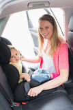 Mother securing her baby in the car seat. In her car Royalty Free Stock Image