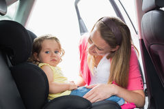Mother securing her baby in the car seat. In her car Stock Photography