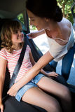 Mother securing her daughter with seat belt. In a car Royalty Free Stock Photo
