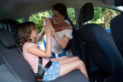 Mother securing her daughter with seat belt. In a car Stock Photo