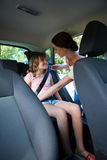 Mother securing her daughter with seat belt. In a car Stock Image