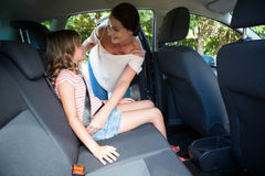 Mother securing her daughter with seat belt. In a car Stock Photos