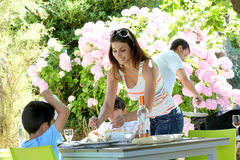 Mother serving children lunch in the garden Stock Photography
