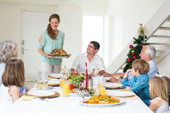 Mother serving Christmas meal to family. At dining table Stock Images