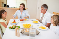 Mother serving dinner to family. Mother serving dinner to her family Royalty Free Stock Image