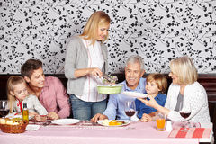 Mother serving food to family at Royalty Free Stock Images