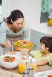 Mother serving food to son Royalty Free Stock Image