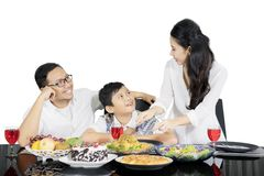 Mother serving meals for her family on studio Royalty Free Stock Photos