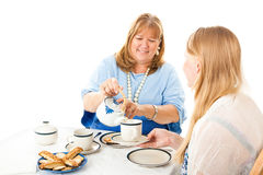 Mother Serving Tea to Daughter Stock Photos